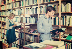 Young smiling man reading book while. Smiling cheerful positive men reading book while choosing it in book shop Stock Photos