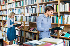 Young smiling man reading book while. Smiling cheerful positive men reading book while choosing it in book shop Stock Image