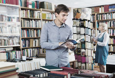 Young smiling man reading book while. Young smiling cheerful positive men reading book while choosing it in book shop Royalty Free Stock Photo