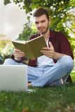 Young man reading book in the park. Young smiling man reading book in the park, preparing for exams at the university or college sitting on the grass with his Royalty Free Stock Photography