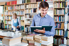 Young smiling man reading book while. Young positive men reading book while choosing it in book shop Royalty Free Stock Photo