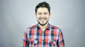 Young smiling man in a red checkered shirt on grey background stock video