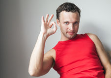 Young smiling man in red shirt shows okay gesture Stock Photos