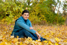 Young smiling man relaxing in autumn park. Royalty Free Stock Images