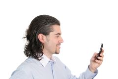 Young smiling man's profile with phone in hand. Profile of smiling young dark haired man in light blue striped shirt with cell phone  isolated on white Royalty Free Stock Images