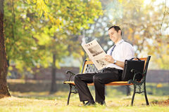 Young smiling man seated on bench reading newspaper in a park Royalty Free Stock Photos