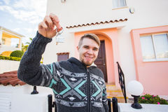Young smiling man showing keys to new home. Real estate, apartment and people concept Royalty Free Stock Photo