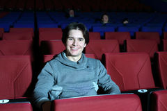Young smiling man sits in big cinema theater stock photo