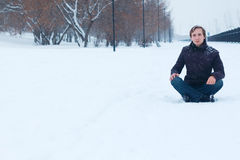 Young smiling man sits on snowy road near park at winter Stock Photo