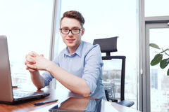 Young smiling man sitting at desk in office Royalty Free Stock Photos