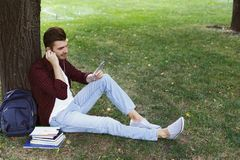 Young man listening to music on the grass outdoors. Young smiling man sitting on the grass, using smartphone and listening to music with earphones outdoors Stock Photos
