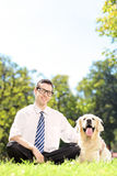 Young smiling man sitting on a green grass next to his dog in a Royalty Free Stock Images