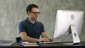 Young smiling man sitting at his desk in the office and working on the computer. stock footage