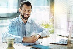 Young smiling man sitting by the table and worksing. In the office. Young busy smiling man sitting in the office by the table working with papers and laptop and Royalty Free Stock Photos