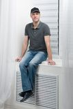 Young smiling man sitting on a white window Stock Photography