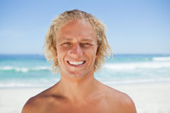 Young smiling man standing on the beach Stock Images