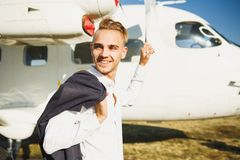 A young smiling man stands near an airplane. Small aircraft for private travel royalty free stock photo