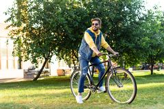 Young smiling man in sunglasses riding retro bicycle. In park stock photography