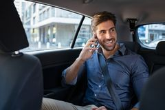Young man talking over phone in taxi. Young smiling man talking over phone while sitting in taxi. Handsome business man in formal clothing sitting on back seat royalty free stock image