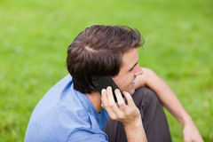 Young smiling man talking on the phone while sitting in a park Royalty Free Stock Image