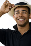 Young smiling man tipping hat. Young smiling hispanic male tipping his hat, vertical portrait Royalty Free Stock Images