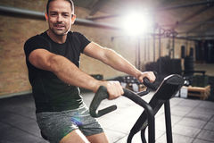 Young smiling man training on cycling machine Stock Photo