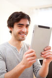 Young smiling man using a tablet Royalty Free Stock Image