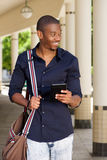 Young smiling man walking with cellphone and bag. Portrait of young smiling man walking with cellphone and bag Stock Images