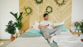Young smiling man watching television with TV control in hand and call his wife to join him. On bed Stock Image