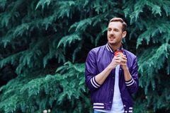 Man in the forest against green tree background with cup of coffee. Young smiling man wearing the purple blazer is drinking coffee from red cup in the forest stock image