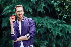 Man in the forest against green tree background with cup of coffee. Young smiling man wearing the purple blazer is drinking coffee from red cup in the forest royalty free stock images