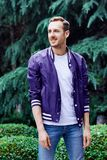 Man in the forest against green tree background. Young smiling man wearing the purple blazer in the forest standing against green tree background stock photo