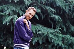 Man in the forest against green tree background. Young smiling man wearing the purple blazer in the forest standing against green tree background crosses his royalty free stock images
