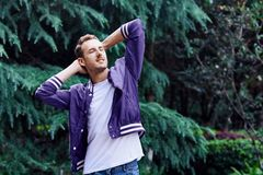 Man in the forest against green tree background. Young smiling man wearing the purple blazer in the forest standing against green tree background with his hands royalty free stock images