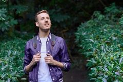 Man traveling in the forest with backpack. Young smiling man wearing the purple blazer is walking in the forest with gray backpack holding his jacket stock images