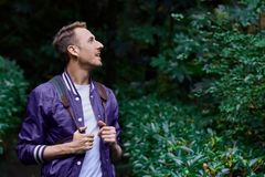 Man traveling in the forest with backpack. Young smiling man wearing the purple blazer is walking in the forest with gray backpack holding his jacket stock photography