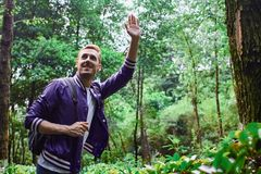 Man traveling in the forest with backpack. Young smiling man wearing the purple blazer is walking in the forest with gray backpack royalty free stock photography