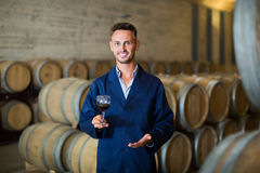 Young smiling man winery expert  holding glass of wine Royalty Free Stock Photo
