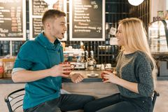 Young smiling man and woman together talking in coffee shop sitting near bar counter, couple of friends drinking tea, coffee stock image