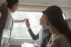 Young smiling man and women using phone on a train, Beijing Stock Photography