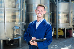 Young smiling man working in winery and taking notes Stock Photography
