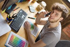 Young smiling man working at his workplace stock photos