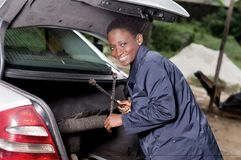Young smiling mechanic with a working tool. Young smiling mechanic takes her tool from the back of a car in the garage Royalty Free Stock Images