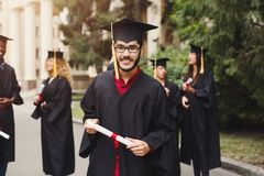 Happy young man on his graduation day. Young smiling men on his graduation day in university, standing with multiethnic group of students. Education Royalty Free Stock Photos