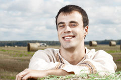 Young smiling men in national belorussian costume. Young smiling man in national belorussian costume resting on a haystack Stock Image