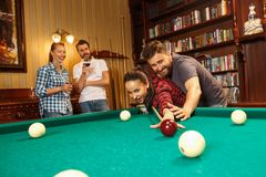 Young men and women playing billiards at office after work. Young smiling men and women playing billiards at office or home after work. Business colleagues Royalty Free Stock Images