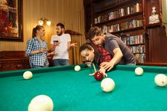 Young men and women playing billiards at office after work. Young smiling men and women playing billiards at office or home after work. Business colleagues Stock Photos