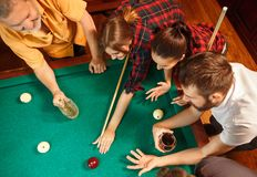 Young men and women playing billiards at office after work. Young smiling men and women playing billiards at office or home after work. Business colleagues Royalty Free Stock Photo