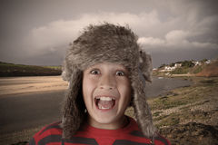 Young smiling boy in furry hat Royalty Free Stock Photography