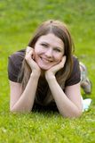 Young smiling model. Young smiling girl lying on the grass in the park Stock Photography